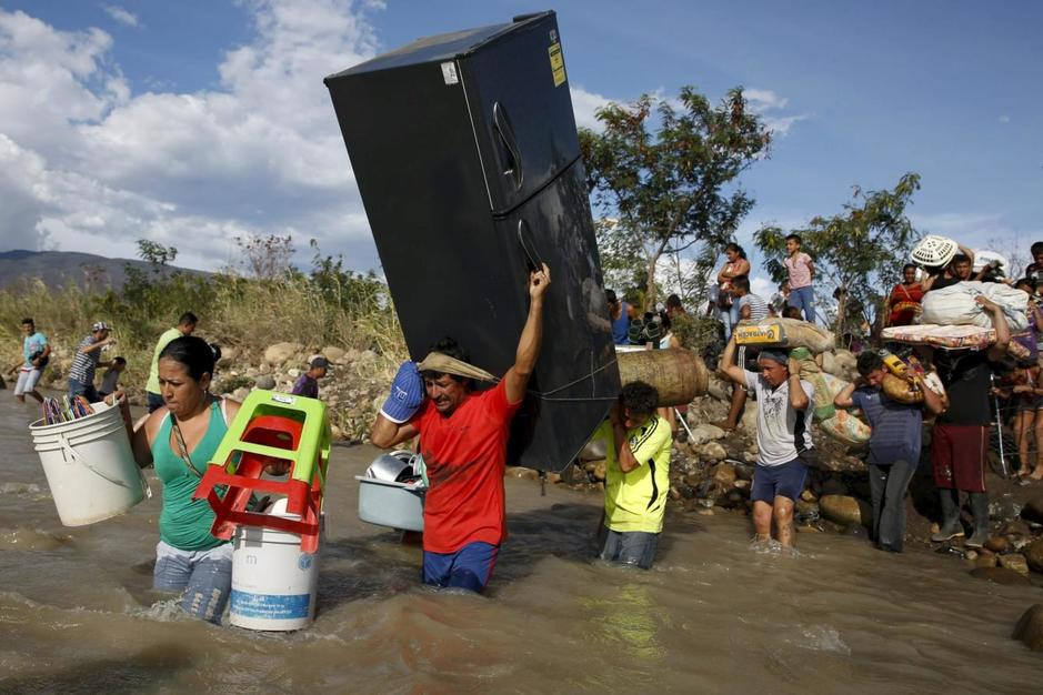 a-man-carries-a-refrigerator-alongside-people-carrying-their-belongings-to-colombia-through-the-tachira-river-at-san-antonio-in-tachira-state-venezuela (1)